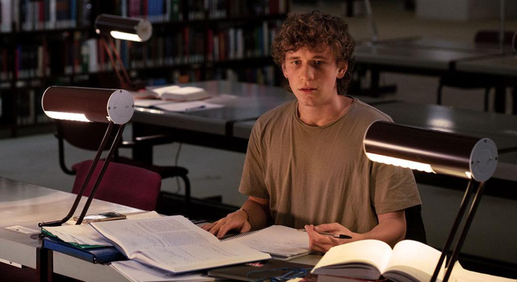 Junger Mann lernt in Bibliothek